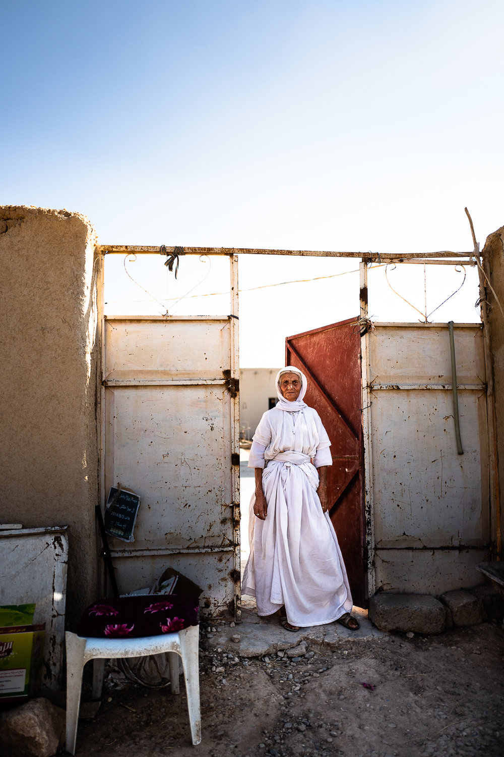 An elder yazidi woman in front at her distroyed house under the Sinjar mount.