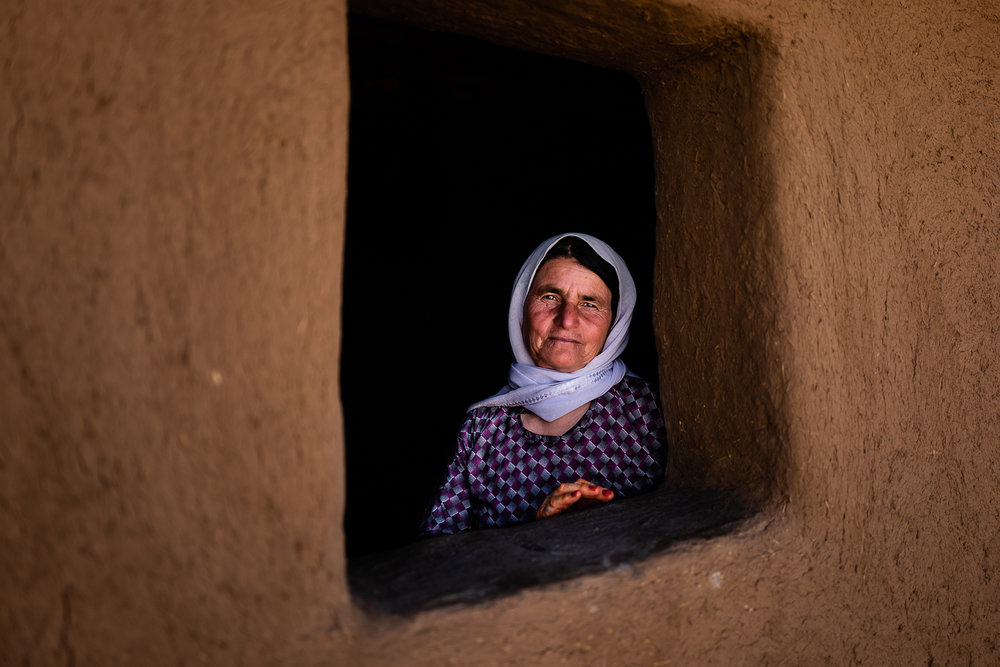 An elder yazidi woman at the window of her mud house in a unofficial camp in Sharya, near Dohuk