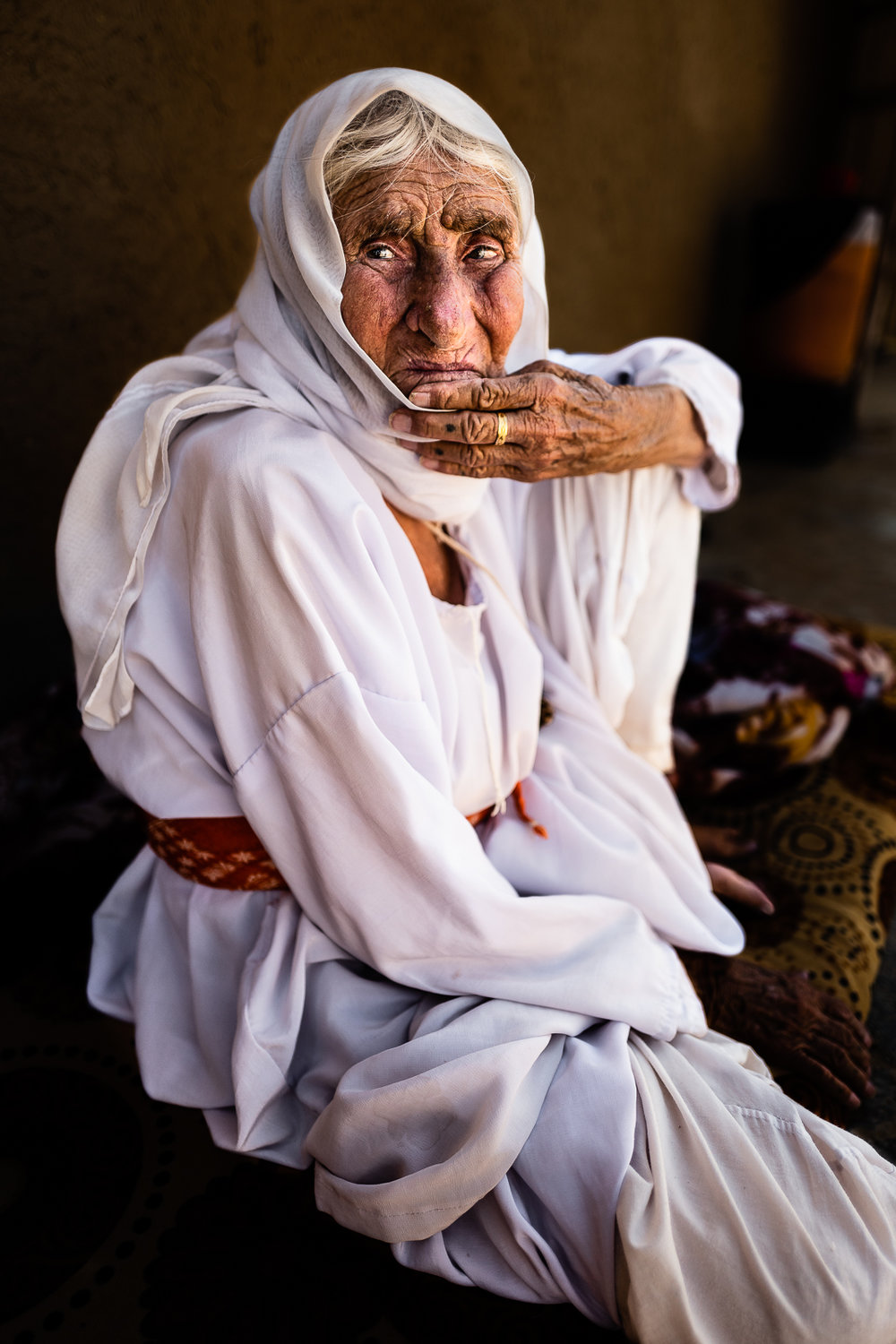 An old woman sits outside her mud house in a unofficial camp in Sharya, near Dohuk