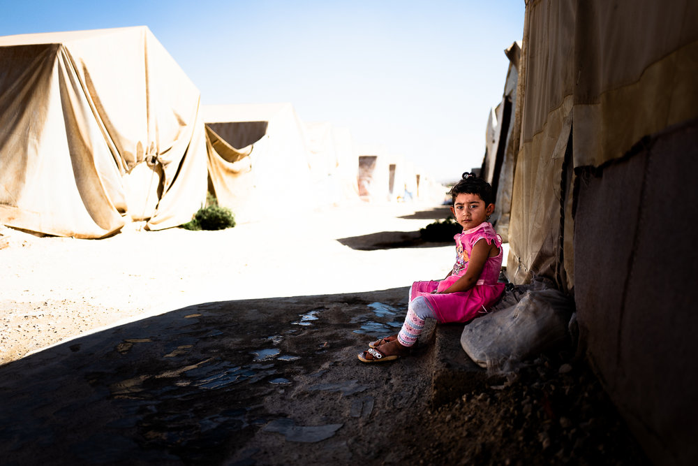 A little Yazidi girl sitting alone in the middle of the tents of Khanik refugees camp, near Douhk