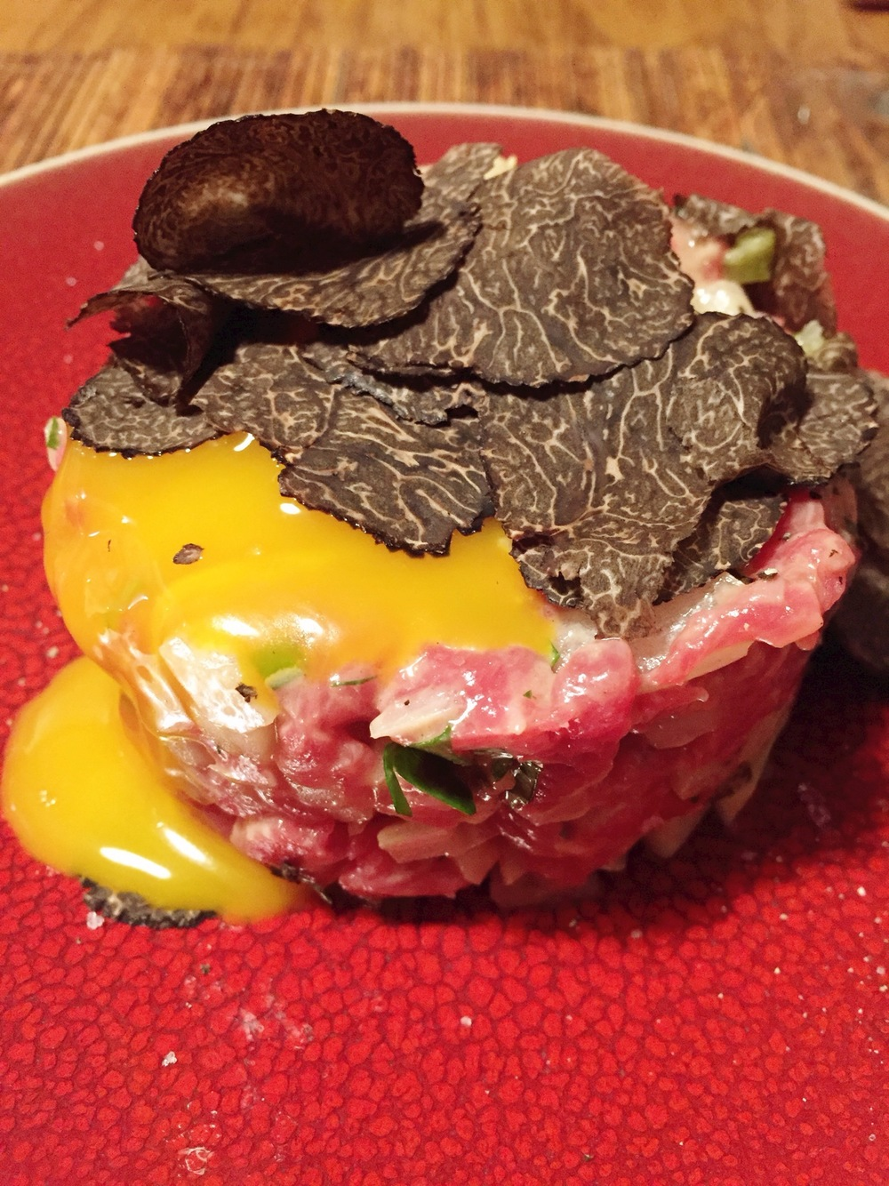 Steak tartare with egg yolk and shaved black truffle with...