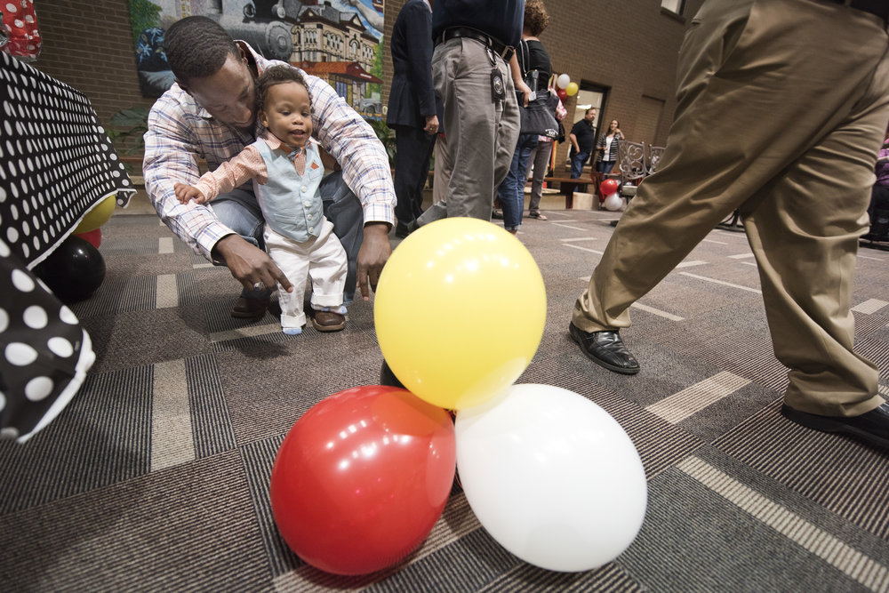 Jaxon Burton, 1, is enthralled by balloons strewn around the lobby while hanging out with his dad Cleva Burton during the Brazos County Adoption Day event, Tuesday, Nov. 15, 2016, at the Brazos County Administration Building in Downtown Bryan, Texas.