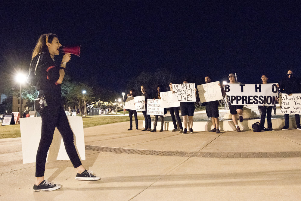 Freshman political science and pre-law major Morgan Gimblet, left, speaks over a megaphone while others stand around the Fish-Pond with signs during a anti-oppression protest held Wednesday evening, Nov. 17, 2016, on Texas A&M's campus in College Station, Texas.