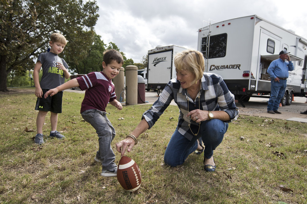 Houston area resident and Texas A&M class of 1976 graduate Mary Ellen Wollam holds a football for grandson Tyler (4) to kick, while another grandson, Linc (5), looks on, Tuesday, Nov. 22, 2016 at the parking lot at Olsen Field in College Station, Texas.