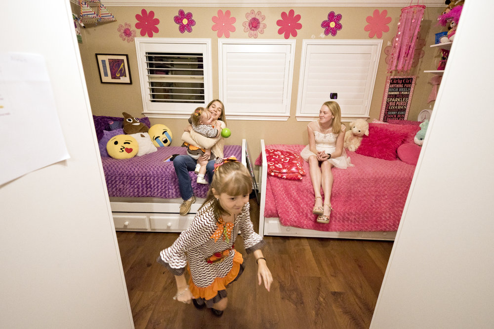 Ava Adams, 7, darts back to her side of the room, while her sister Alexis, 14, holds one-year-old Pippen, and Kaelee, 12, looks on Tuesday, Nov. 22, at the Adam's home in Cypress, Texas.