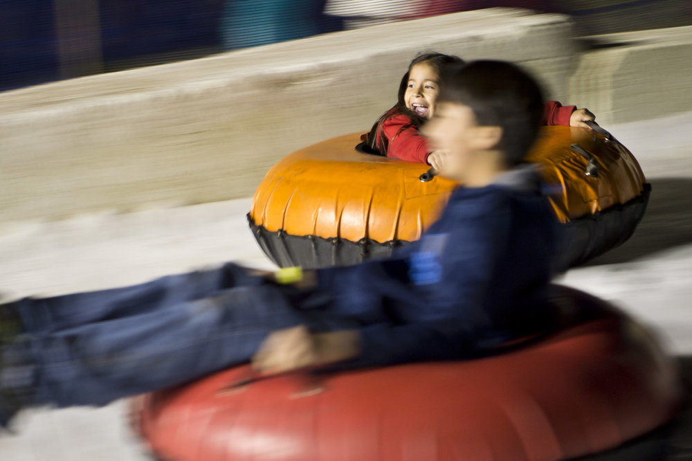 Katya, 5, and her brother Kevin Garcia, 13, race down the snow bank Thursday evening, Dec. 1, 2016, at the Holiday Magic! event at Sue Haswell Park in Bryan, Texas.