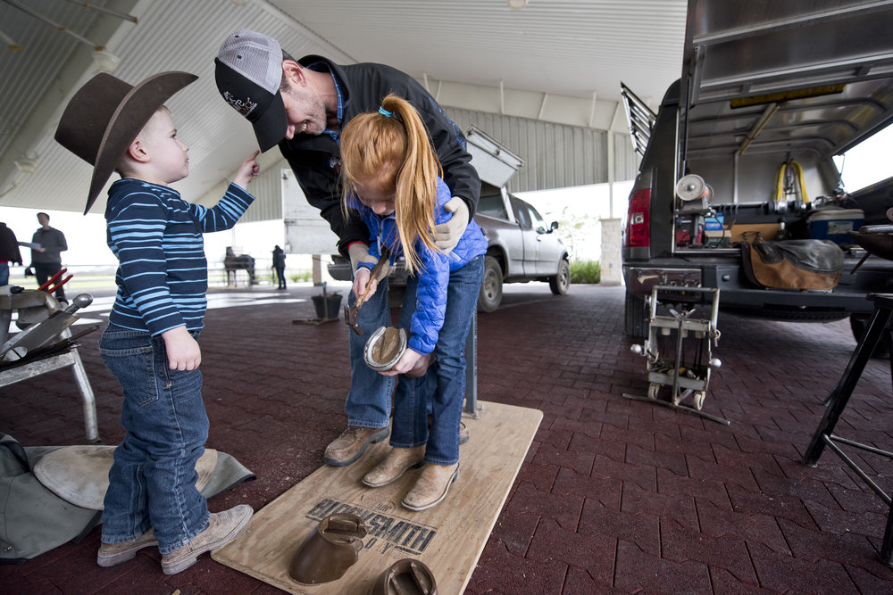 Cade Shepard, with the Texas Equine Hospital, helps Cayle Canon, 8, drive a nail into a dummy hoof while her brother Keslee Canon, 4, tries to get Shepard�s attention Saturday during the Aggie Horse Fair at the Hildebrand Equine Complex in Bryan.