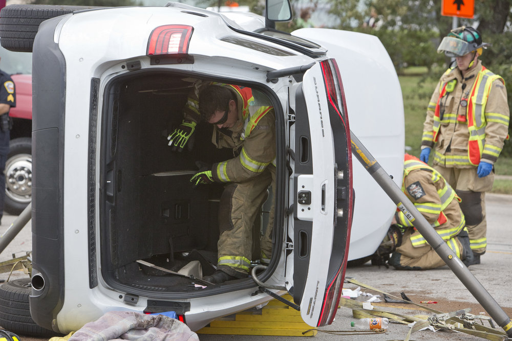 A Bryan first responder climbs through the cabin of a flipped vehicle at the scene of a wreck on East Villa Maria Road, in front of the Blinn College campus. The driver of the flipped vehicle pulled out onto Villa Maria and was struck by another vehicle. The extracted occupant was transported to Saint Josephs Hospital with minor injuries, and was later released.