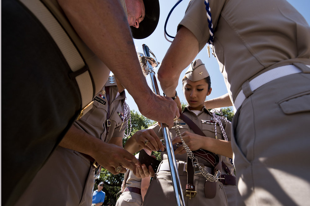 Texas A&M University Corp of Cadets member help new Commander for the 2016-2017 academic year Cecille Sorio strap on her sword holster before beginning their march to Simpson Drill Field for the second Pass in Review, Saturday, May 7, 2016, in the Quad on Texas A&M's campus in College Station, Texas.