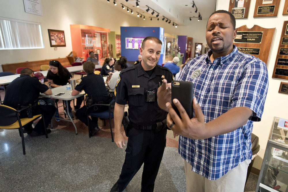 "Bryan Police Sgt. Jason James, left, and Quinton Samuels, a mentor with Young Men in Unity, broadcast on Facebook Live urging locals to come to come to the Brazos Valley African American Museum for ""Lunch with Law Enforcement,"" Saturday, July 23, 2016, in Bryan, Texas."