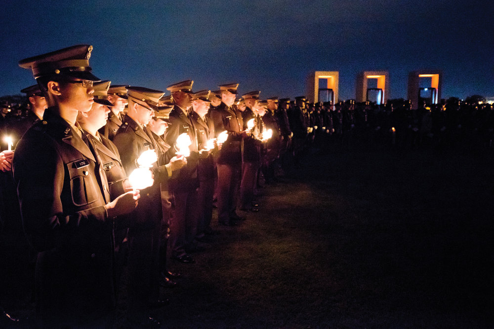 Corp of Cadet members keep candles lit in the wind during Texas A&M University's Bonfire Remembrance Ceremony early Friday morning, Nov. 18, 2016, at the Bonfire Memorial site in College Station, Texas.