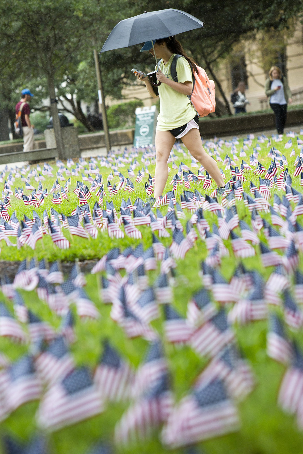 Texas A&M junior sociology major Madi De Amaral make her way through the the Academic Plaza where the university and the Lone Survivor Foundation have set out thousands of flags in an extended Veterans Day observance, Wednesday, Nov. 9, 2016, in College Station, Texas.