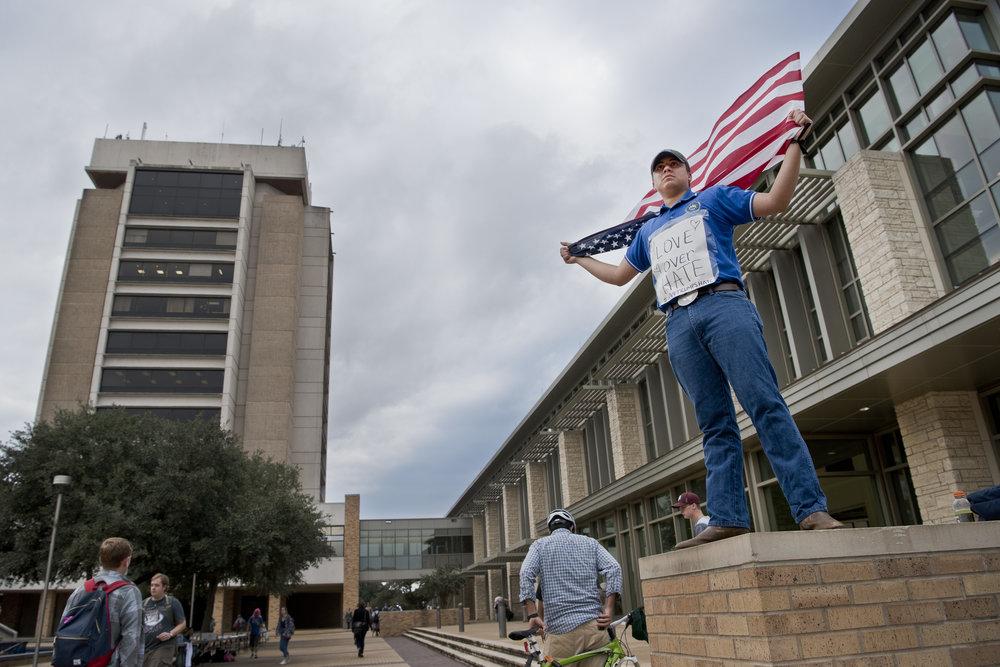 "Texas A&M freshman english student Charlie Abrego hold an American flag over his shoulders while wearing a sign reading ""Love over Hate"" on his torso while other students pass by Wednesday, Nov. 9, 2016, on campus in College Station, Texas."