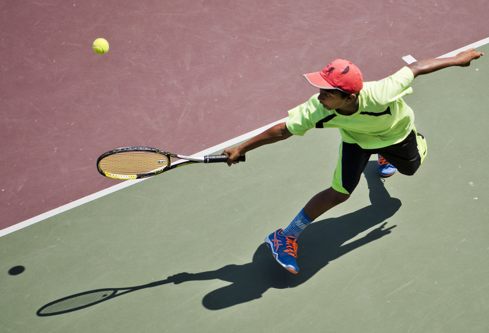 Ritesh Patil, 12, makes an acrobatic save on a volley from Lucas Brown, not pictured, during the boys 12-year old doubles championship match, Thursday, June 16, 2016, at The Capsher Texas Grand Slam tournament at the Mitchell Tennis Center at Texas A&M University in College Station, Texas.