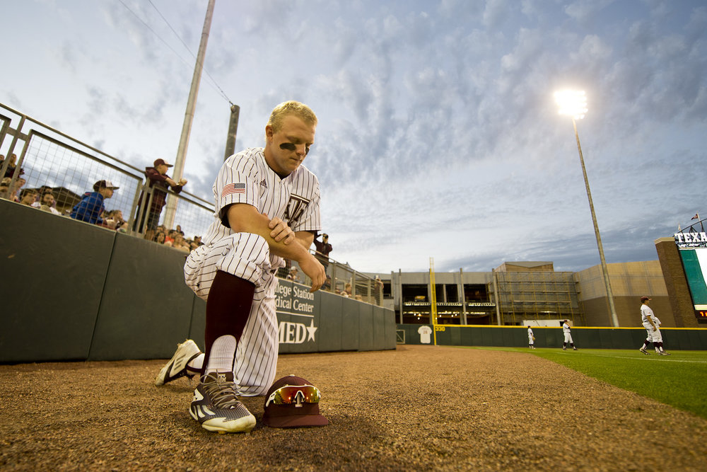Texas A&M University third baseman Boomer White prays while his teammates warm up for a game against Louisiana State University, Friday night, at Blue Bell Park in College Station, Texas.