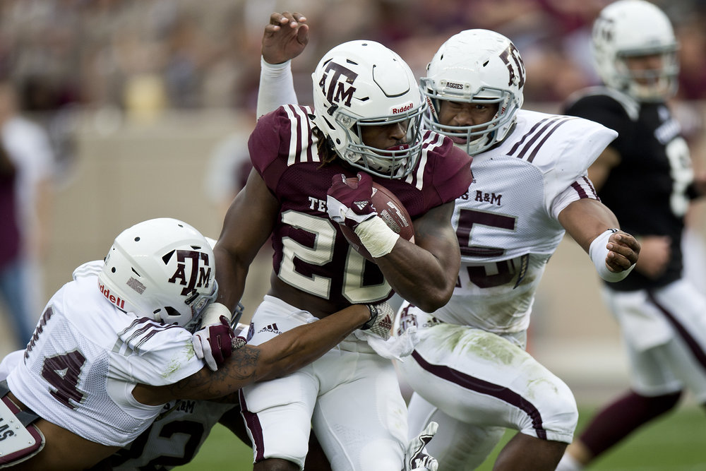 Texas A&M University Myles Garrett (15) bears down on running back  James White (20) while defensive back Justin Evans (14) gets a hand in during Texas A&M's Spring game, Saturday, April 9, 2016, at Kyle Field in College Station, Texas.