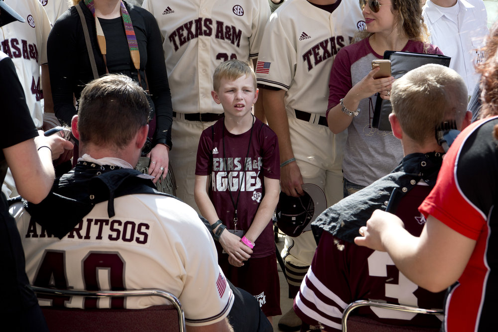 Hunter Willett, 8, isn't too sure about Landon Miner (33) and Chris Andritsos' (40) new haircuts as the two have their heads shaved at the Texas A&M baseball team's BTHO Breast Cancer 2017 event, Saturday, Feb. 11, 2017, at Olsen Field in College Station, Texas.