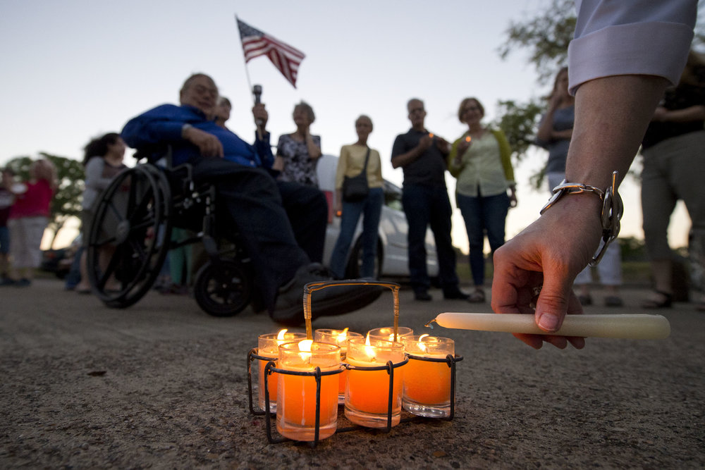 Elizabeth C. Berigan, a physician at The Internal Medicine Center in Bryan, Texas, lights a candle while others gather around during a candle-lit vigil for the Affordable Care Act, held Wednesday evening, March 22, 2017, in front of Texas State Representative Bill Flores's Bryan office on Briarcrest Boulevard in Bryan, Texas.