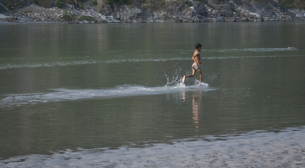 Boy running and playing in the Ganges