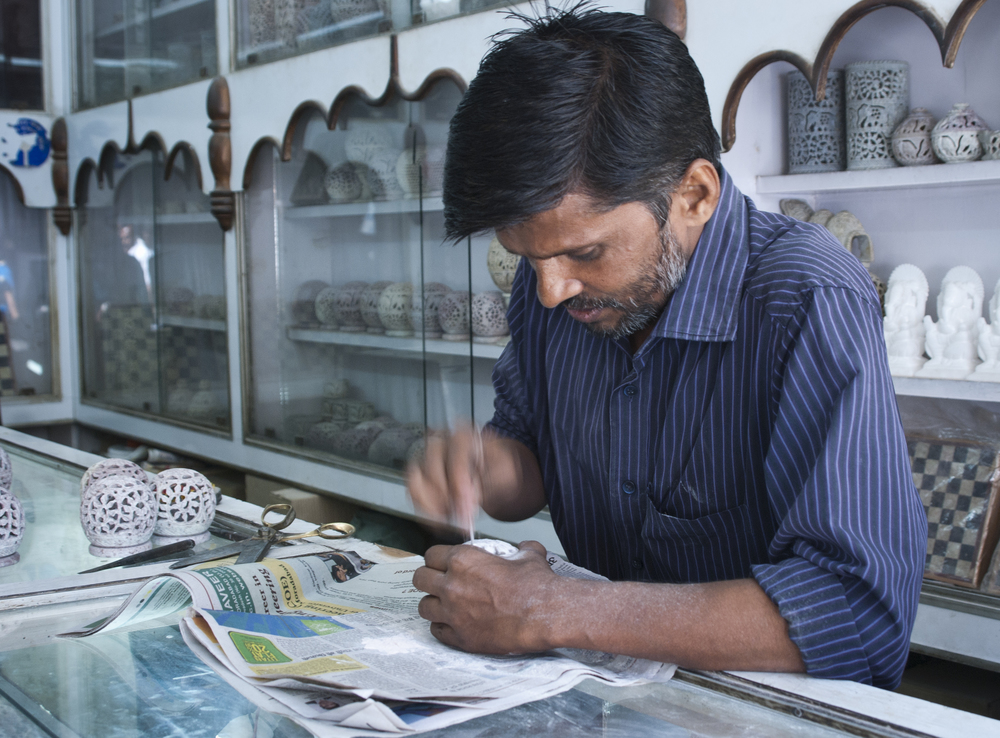 Artisan crafts are often found in the shops. This man is hand carving a candle lantern.