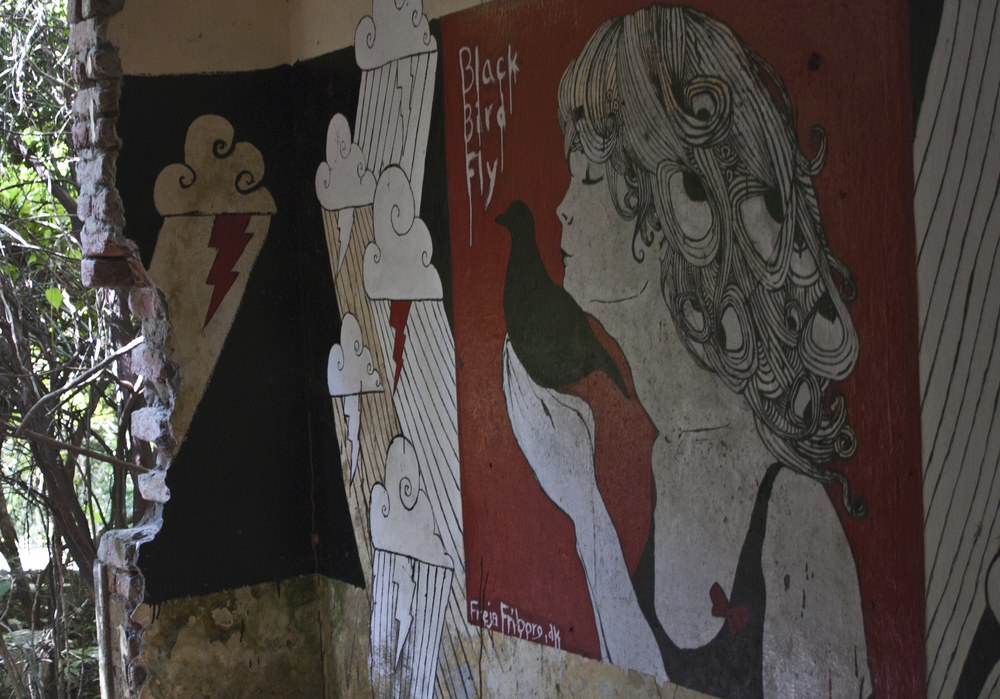 Artwork memorializing The Beatles' time at the Ashram decorates the remnants of the buildings.