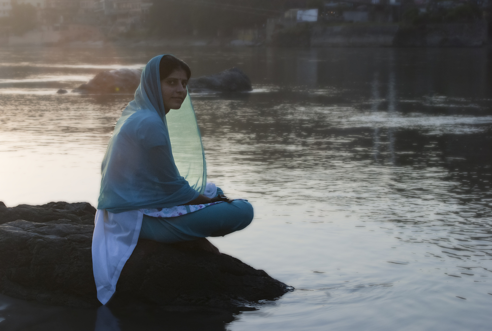 A woman sits peacefully and reflects along the banks of the Ganges.