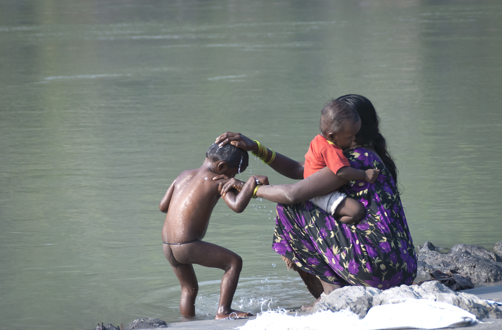 A woman bathes her child in the Holy water of the Ganges