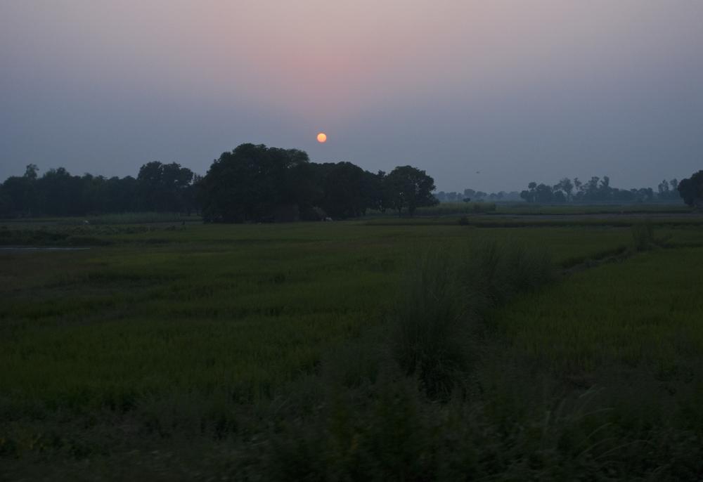 Sun sets as the train speeds by open fields.