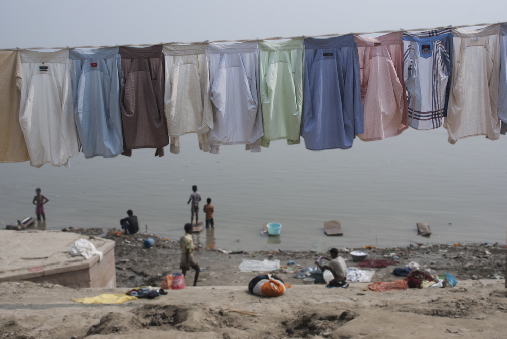 Brightly colored shirts hang to dry in the sun along the ghats of Varanasi.