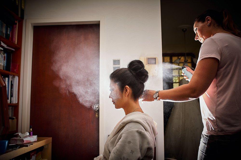 Foto van de bruid tijdens de voorbereidingen. Een trigger op de X100F en een flitser achter de bruid zorgen er voor dat je de spray goed te zien krijgt.