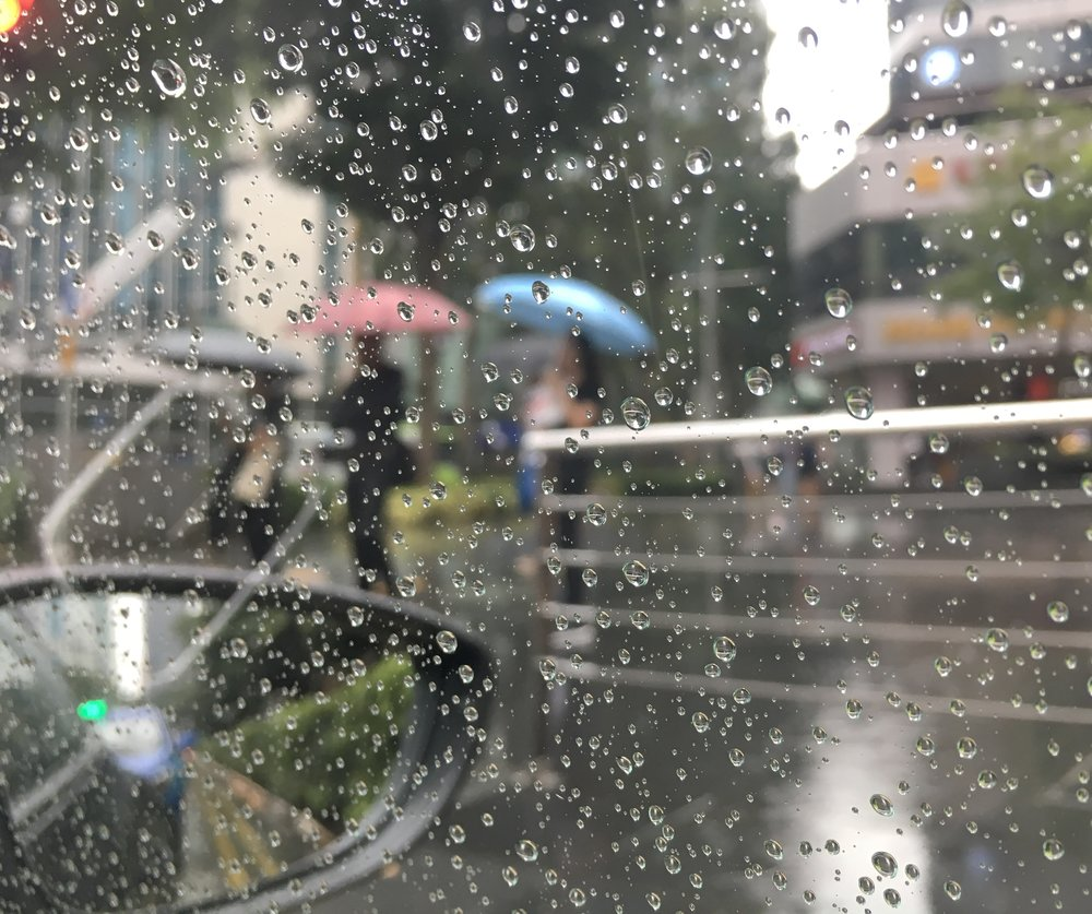 © Naida Ginnane 2018  Shot from inside my car while waiting at the lights. There's a lot going on with this photo. I chose to direct the focus to the raindrops on the window so that the background would be nicely blurred. We can still make out the umbrella shapes on the left. We also have the rear vision mirror and reflections on the glass in the foreground o create a sense of depth.  iPhone 6 with Camera + App
