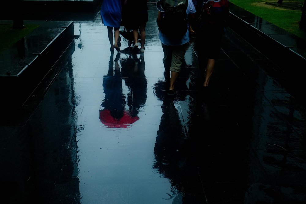 © Sean Ginnane 2018  Despite being very dark, this image has a lovely red focal point at the red umbrella with a nice framing effect on either side from the dark shadows. The figures are reduced to silhouettes against the light sky reflected by the water on the footpath. We can still see them huddling under the umbrella to escape the rain.  Fujifilm XT-1, 18-55mm lens