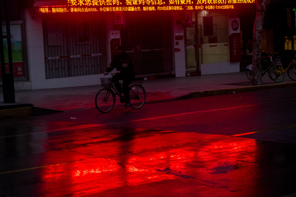 Red Bike ©Sean Ginnane 2018 Fujifilm XT-1, 18-55mm lens  A gorgeous shot taken on an early morning walk in Shanghai this week. Sean has taken advantage of the wet roads reflecting the red neon at the top of the image. The two bands of red colour on the top and bottom of the image, frame the bike rider in the centre. It is strangely dynamic and calm at the same time.