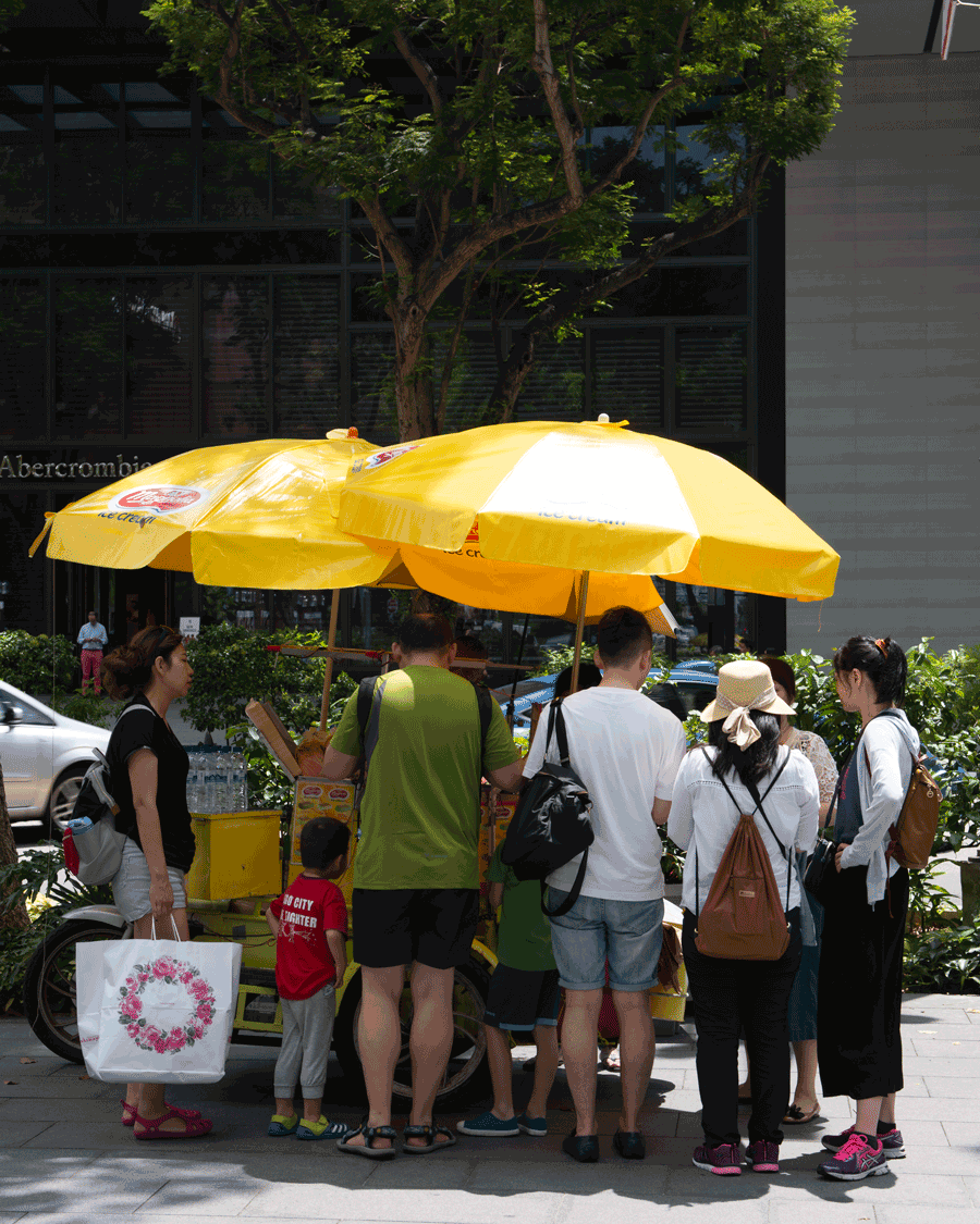 'Yellow Umbrellas' © Naida Ginnane 2018 Nikon D800, 24-70mm lens. f/9.0, 1/125, ISO 100.  A great colour to attract attention, this ice-cream seller uses it as shelter from the sun as well.