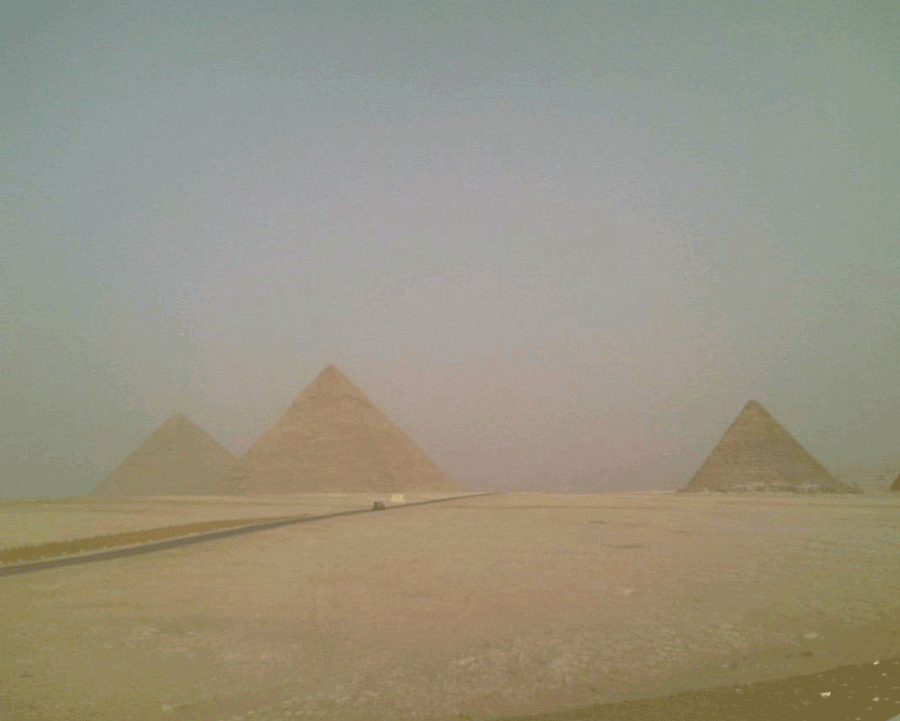 'Pyramids in Sandstorm' © Naida Ginnane 1985.  One of my very old photos, but a great example of minimalism. The muted colours vary only slightly between the sand, stone and sky, while the pyramid shapes are soften by the dust and sand in the air.