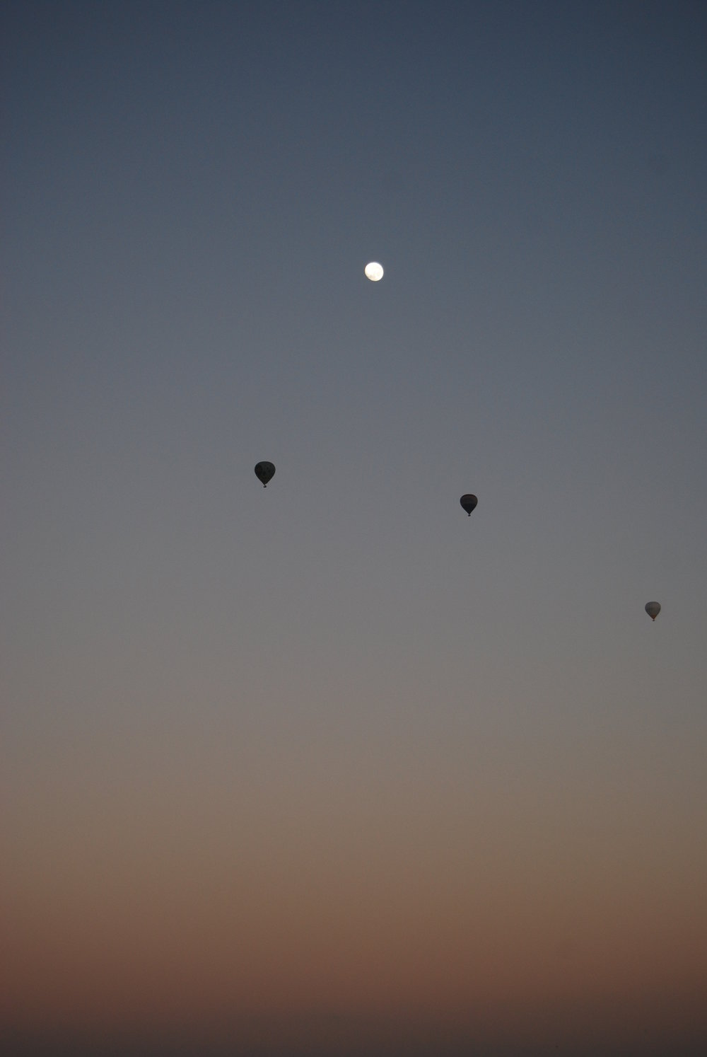 'The Moon and Three Balloons' © Naida Ginnane 2010, Nikon D800, 24-70mm lens. f/5.3, 1/100, ISO 200. Subtle colours and very small shapes create a very peaceful and quiet moment in the early morning sky.