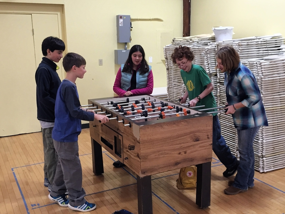 Emily Foster (center) refs a foosball game during recess. She wrote a 50,000-word novel in November, 2014.