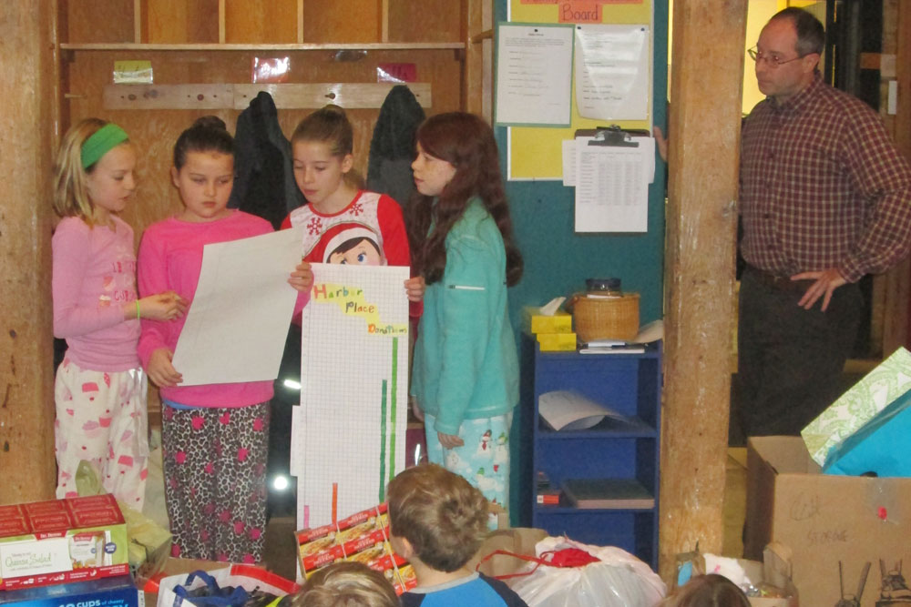Fifth Graders Camryn Muzzy of Burlington, Sabina Nagiba of Colchester, Walker Gray of So. Burlington and Lauren Halberg of Shelburne present the collection data to guest Chris Donnelly of CHT at Friday morning assembly on Dec. 19.