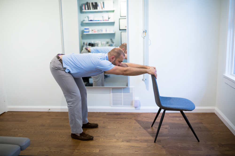 STEP 2:  Make sure your feet are pointing forward. Bend your knees and straighten your back so that you are parallel with the floor. Do not pull on the chair.