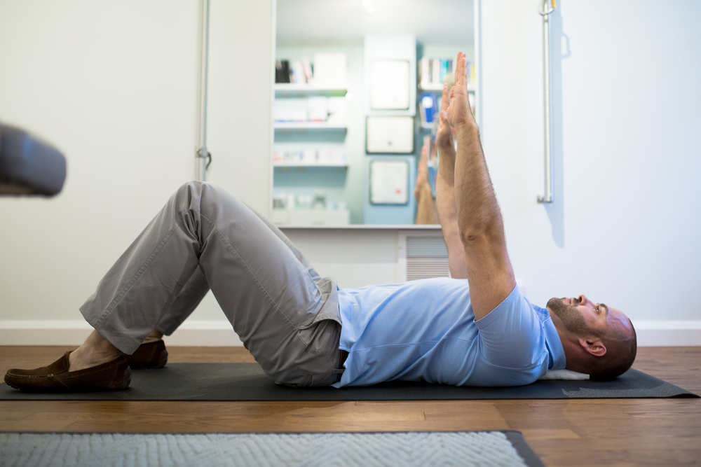 STEP 2:  Bend your knees, perform an abdominal brace and gentle chin tuck (see below). Raise your hands over your shoulders and squeeze the towel with your shoulder blades.