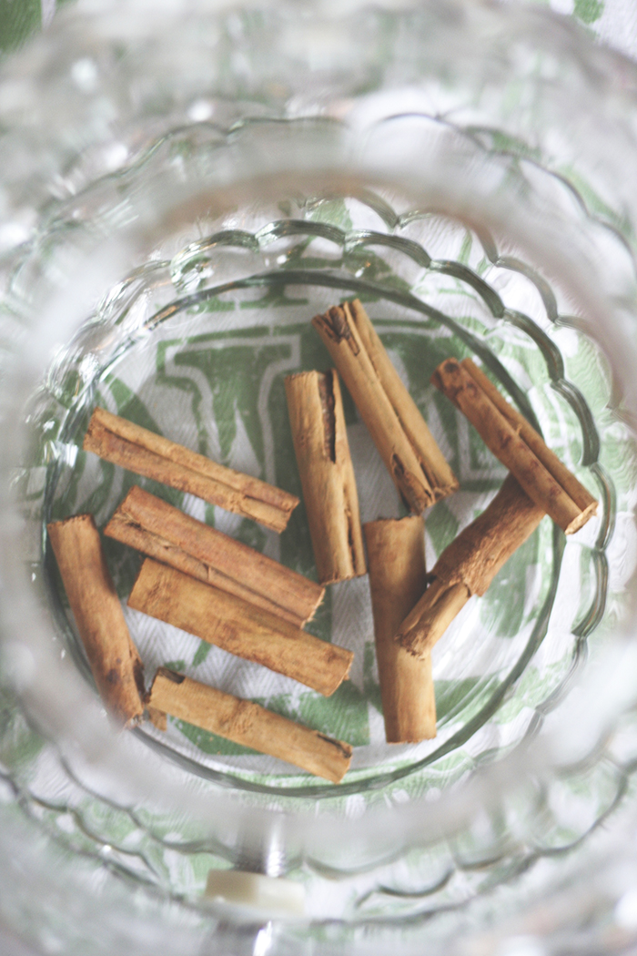 Use a large glass container to hold your whiskey. Something along the lines of a large punch bowl will work perfectly. Drop a handful of cinnamon sticks into the bowl.
