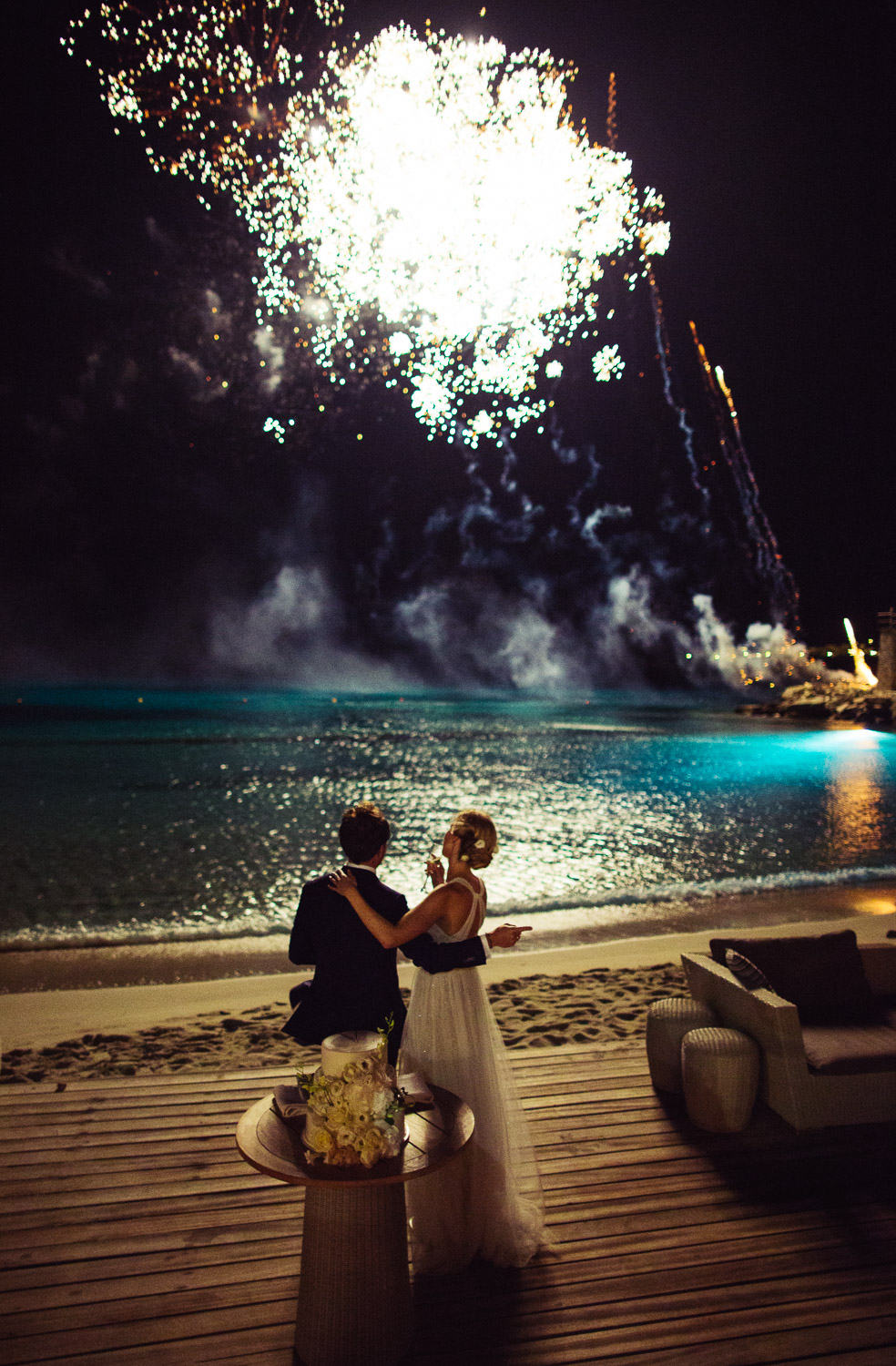 Bride and groom view fireworks display on the beach at Santa Marina Resort's Buddha Bar in Mykonos, Greece