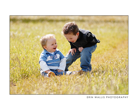 two boys laughing in the grass