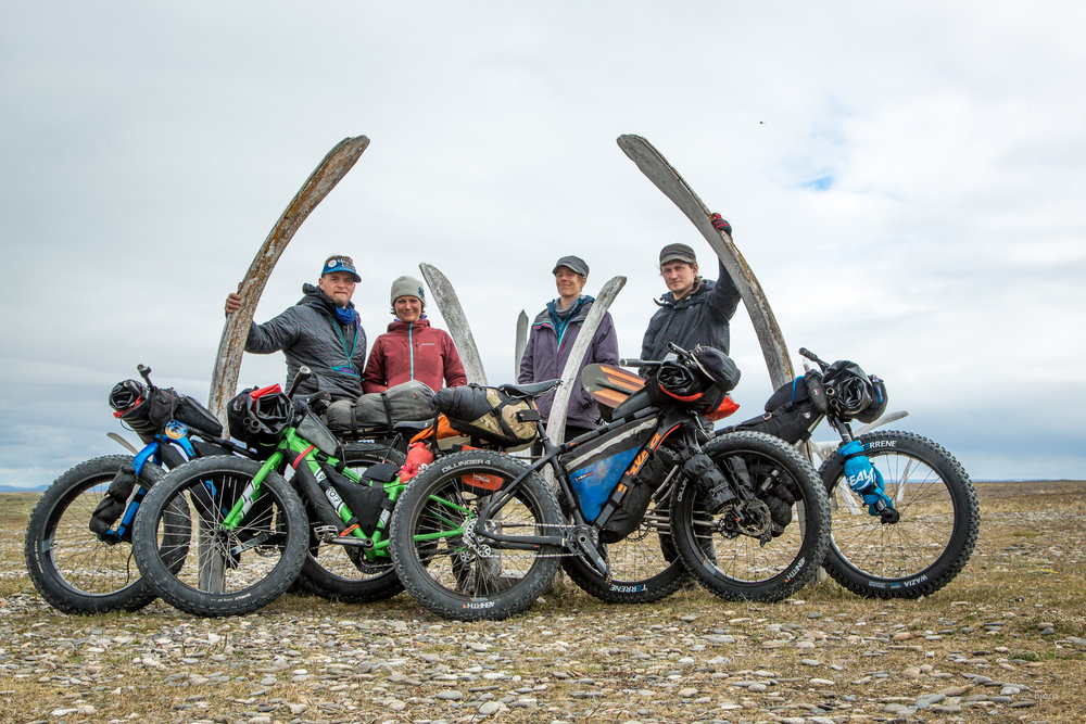 Bjørn Olson, Alayne Tetor, Kim McNett and Daniel Countiss pause in front of a whale bone yard in Point Hope before beginning their fat-bike traverse of the Arctic.
