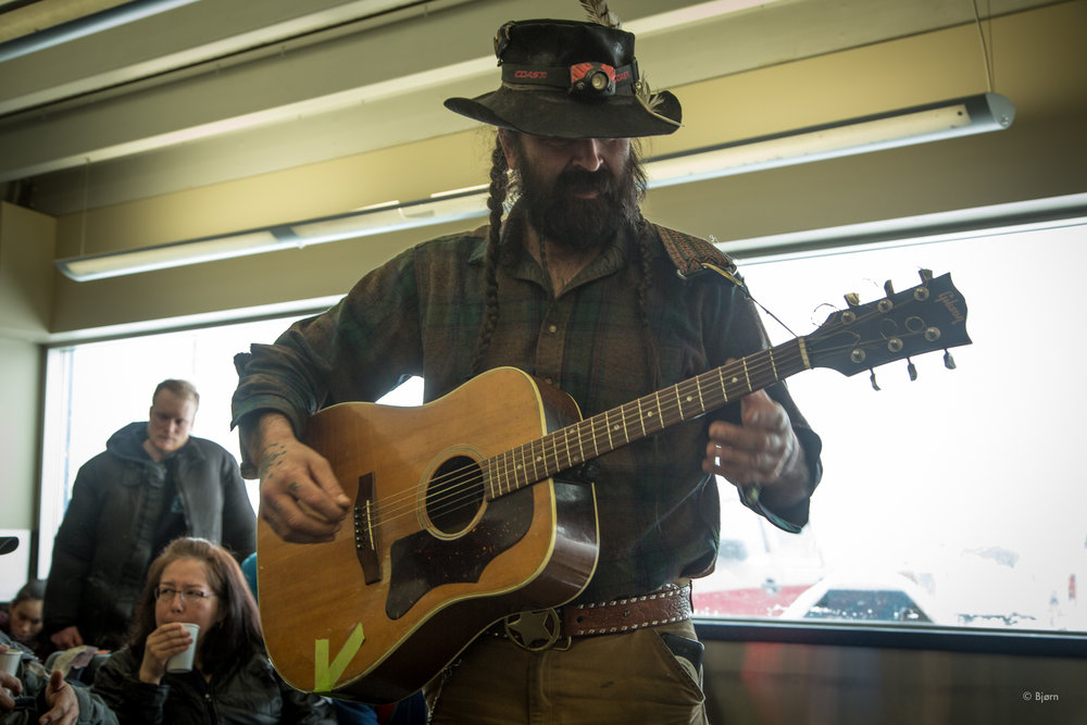 Justin Boot serenaded Tim Osmar, and the rest of us, in the airport, with a song he'd written about Tim's father, Dean.