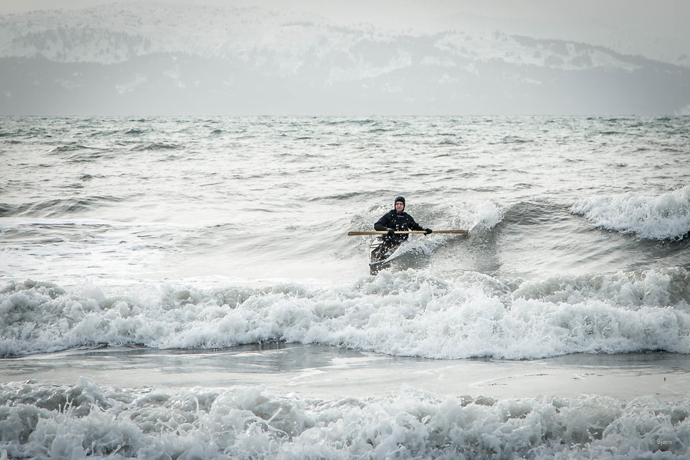 The author surfing his traditional kayak.
