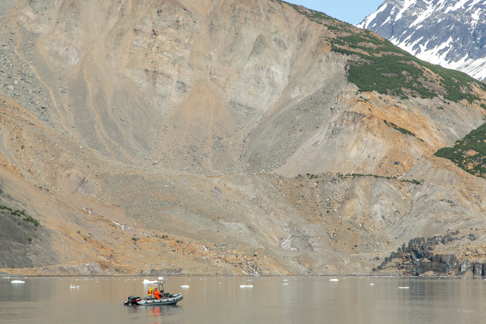 A National Park Service Zodiac passes under the massive landslide that caused the 'mega-tsunami.'