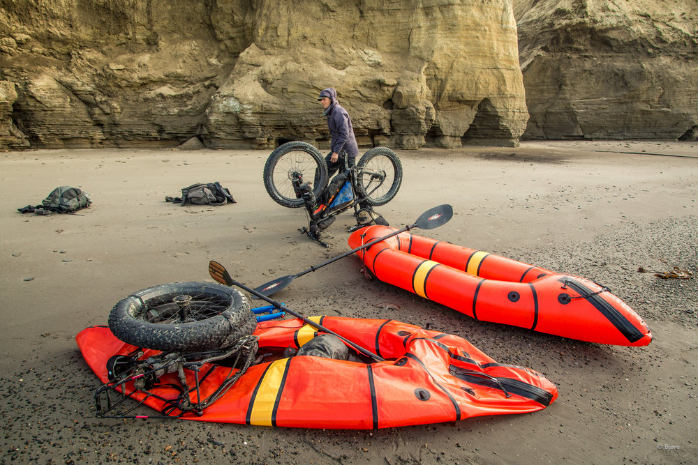 Kim McNett unloads her prototype Alpacka raft - the precursor to the  Caribou  - and prepares to resume biking at the Skull Cliffs in Arctic Alaska.