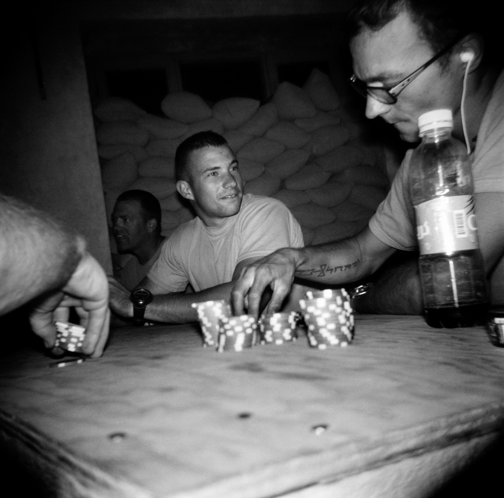 SGT Brian Cattaneo, center, and SPC Joseph Pohl, right, play poker at a COP Charkh in Logar Province.