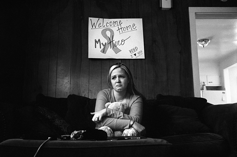 "Stefanie Strausser cries under a ""welcome home"" sign she made for her fiancé SSG Cody Anderson, 25, who was found dead in his apartment in Watertown, New York, 2010."